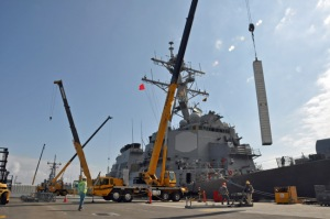 A vertical launch missile canister is loaded onto a guided missile destroyer at the Naval Weapons Station Seal Beach wharf (U.S. Navy photo)>