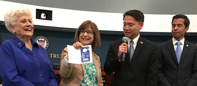 SANDRA MORGAN, holding the city hall parking pass she was awarded, with members of the Westminster City Council Wednesday night. At left is Councilwoman Margie Rice; to Morgan's right are Mayor  Tri Ta and Councilman Sergio Contreras (OC Tribune photo).