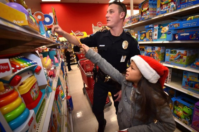Garden Grove PD Officer Chasen Contreras helps Azucena Fuarez, 11, pick out a Batman/Superman toy for her 3-month-old brother during the department's Shop with a Cop event at Target. (Photo by Steven Georges/Behind the Badge OC)