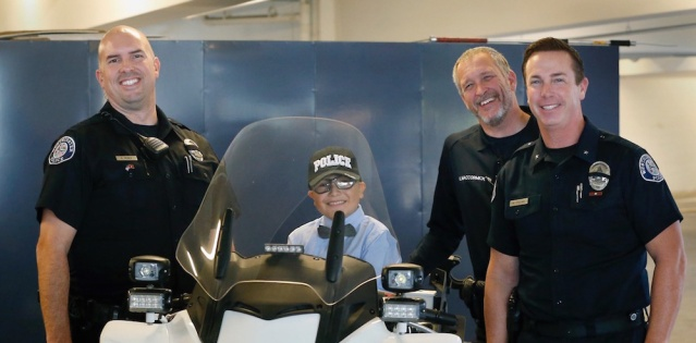 MATEO SANCHEZ, 9, sits on a Westminster PD motorcycle with Officer Roland Perez, Sgt. Kevin MacCormick and Cmdr. Bill Collins. (Photo by Christine Cotter/Behind the Badge OC).