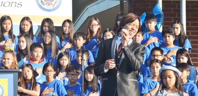 """PHUONG NGUYEN, parent of a Cook School student, sings """"The Star Spangled Banner"""" at Friday's event (OC Tribune photo)."""